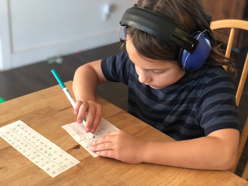Rondel sitting at the kitchen table with sound-reduction headphones, writing out the answer to one of his clues.