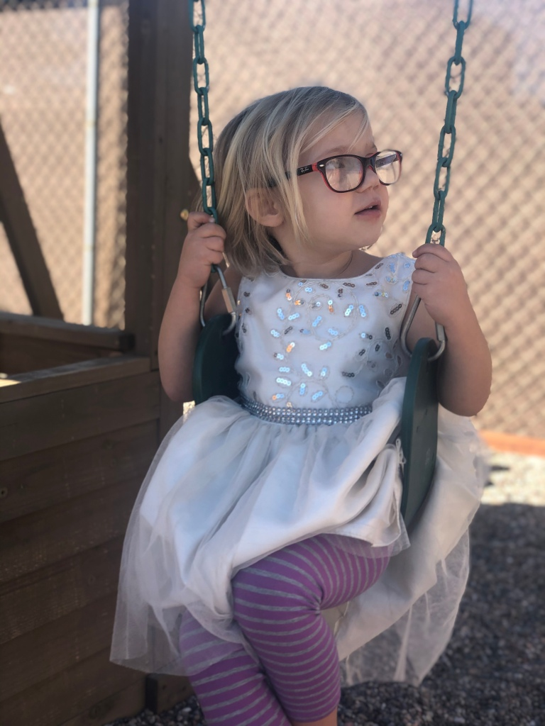 Aubade sitting on a swing in a white dress, striped purple pants, and large red-framed glasses